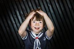 Школьник представляя в костюме матроса с эмоциями стоковое фото