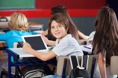 Школьник при таблетка цифров сидя на столе внутри Стоковое Изображение