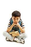 Школьник пробуренный, расстроенный и сокрушанный путем изучать домашнюю работу Мальчик сидя вниз на поле Стоковая Фотография RF