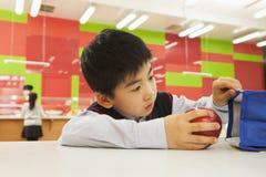 Школьник проверяя сумку обеда в школьном кафетерии стоковое фото