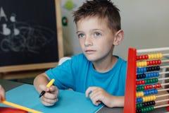Школьник работая на домашней работе математики Стоковые Фотографии RF