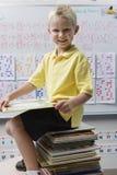 Школьник сидя на стоге книг стоковое изображение