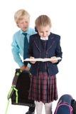 Школьник смотря от задней части школьницы в раскрытой книге в руках ` s девушки, изолированной белой предпосылке Стоковые Изображения