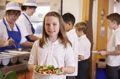 Школьница держа плиту еды в школьном кафетерии стоковое фото