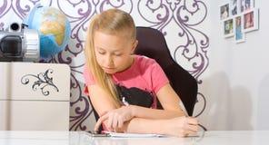 Школьница делая домашнюю работу и смотря на smartphone Стоковая Фотография RF