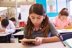 Школьница используя планшет в классе начальной школы Стоковые Изображения RF