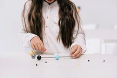 Школьница работая с молекулярной моделью на уроке химии Стоковые Изображения