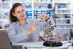 Школьница регулирует модель руки робота Стоковая Фотография RF