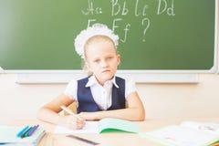 Школьница сидя на столе, классе школы, и книге чтения Стоковые Фотографии RF