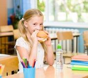 Школьница смотря камеру пока имеющ обед во время пролома Стоковая Фотография