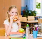 Школьница смотря камеру пока имеющ обед во время пролома Стоковые Фото