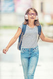Школьница с сумкой, рюкзаком Портрет современной счастливой предназначенной для подростков девушки школы с наушниками и таблеткой Стоковые Изображения