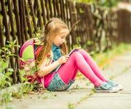 Школьница читая книгу на улице Стоковая Фотография RF