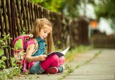 Школьница читая книгу на улице Стоковая Фотография