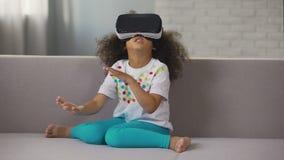 Шлемофон виртуальной реальности Афро-американской девушки нося и игра играть, остатки видеоматериал