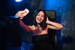 Шлемофон жизнерадостной девушки ленты gamer нося и сидеть около ее компьютера ПК принимая selfie на телефоне во время онлайн стоковые изображения rf