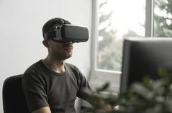 Шлемофон изумленных взглядов виртуальной реальности молодого человека нося, коробка vr и сидеть в офисе против монитора компьютер стоковая фотография rf