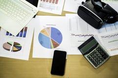 Шлемофон и смартфон взгляда сверху VR с калькулятором, положенным дальше столом с документами продаж и долей темпов роста компани стоковое изображение