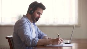 Шлемофон учителя Skype нося смотря экран ноутбука делая примечания видеоматериал