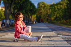 Шлем девушки нося сидя на скейтборде в красивом парке лета Стоковое фото RF