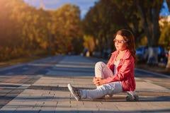 Шлем девушки нося сидя на скейтборде в красивом парке лета Стоковое Изображение RF