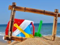 Шлем игрушек и Santas в bamboo рамке на beac Стоковая Фотография RF