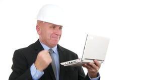 Шлем инженера нося прочитал хорошие новости на ноутбуке и делает жесты рукой победы видеоматериал
