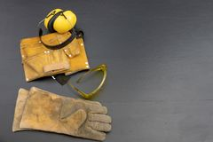 Шлем и перчатки на черном верстаке Одежда работы для constr стоковая фотография rf