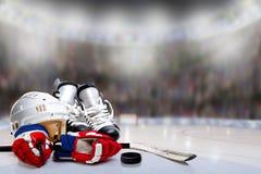 Шлем, коньки, перчатки, ручка и шайба хоккея на льде в катке Стоковые Фотографии RF