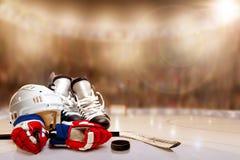 Шлем, коньки, перчатки, ручка и шайба хоккея на льде в катке Стоковые Фото