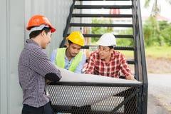 Шлем носки 3 инженеров сидит на лестнице и смотрит план строительства или светокопию в белой бумаге Стоковое Изображение