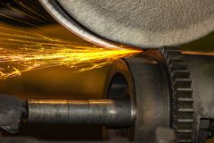 Шлифовальный станок крупного плана, меля с искрами шестерня катит внутри автомобильную промышленность стоковое изображение rf