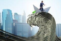Шлюпка бумаги бизнесмена ехать в море доллара стоковое изображение