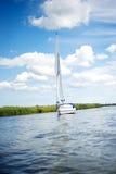 Шлюпка ветрила Норфолка Broads плавая вниз с реки Стоковое Изображение RF