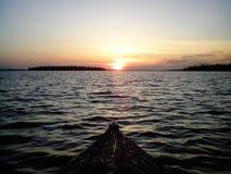 шлюпка возглавляет для захода солнца на малых волнах Стоковая Фотография RF
