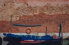 Шлюпка в канале старой краснокоричневой кирпичной стеной, в Венеции, Италия стоковая фотография