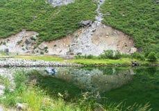 Шлюпка и живописные утесы отражены в чистой воде, Lofoten, Норвегии Стоковое Изображение RF
