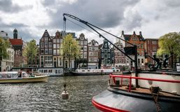 Шлюпка круиза туристская в канале Damrak в Амстердаме на заходе солнца Стоковые Фотографии RF