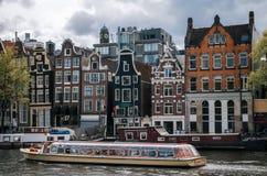 Шлюпка круиза туристская в канале Damrak в Амстердаме на заходе солнца Стоковые Фото