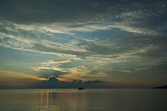 Шлюпка на заходе солнца и восходе солнца с драматическим небом над океаном стоковые изображения