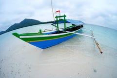 Шлюпка на песке seashore белом и ясном открытом море с славной предпосылкой зеленых холмов Стоковая Фотография RF