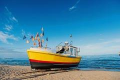 Шлюпка на пляже в Гданьске, Польше песка Маломерное судно на береге моря на голубом небе Сосуд и водный транспорт каникула террит стоковое изображение