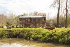Шлюпка на траве и деревянный дом в del Parana перепада, Tigre Буэносе-Айрес Аргентине стоковое фото rf