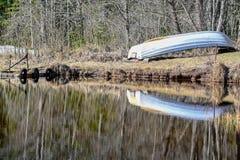 Шлюпка отражая в воде ждать весной стоковое изображение