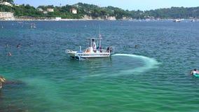 Шлюпка очищает воду в Villefranche-sur-Mer видеоматериал