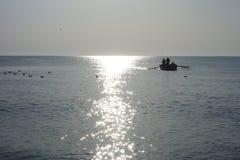 Шлюпка при рыболовы приходя к seashore на восходе солнца после удить оффшорный Стоковая Фотография RF