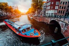 Шлюпка путешествия на известном голландском канале на вечере захода солнца Традиционные голландские мосты и средневековые дома am стоковое изображение rf