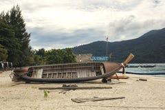 Шлюпка ремонтируя на пляже стоковое фото rf