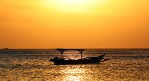 Шлюпка рыболова в Бали, Индонезии во время золотого захода солнца Океан и небо выглядеть как золото стоковое изображение