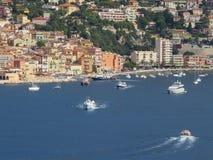 Шлюпки и яхты плавая в среднеземноморском Прибрежный город славного стоковые фото